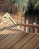 Liegestuhl aus Holzlamellen auf Holzterrasse