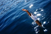 A boy jumping into water
