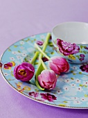 Tulips on a plate next to a matching bowl with a floral pattern