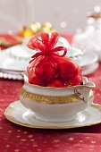 A red sack filled with Christmas baubles in a white sugar bowl