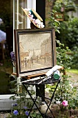 A framed picture and painting utensils on a small table in the open air