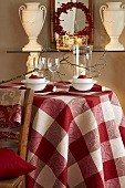 An autumnal table laid with a checked cloth, pomegranates and a lantern
