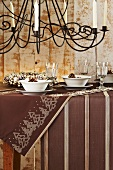 A Christmas table laid with a brown cloth with a wrought iron chandelier hanging above