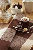 A cup of cappuccino on a brown checked table cloth
