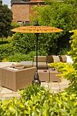 Korbmöbel auf Terrasse unter gelbem Sonnenschirm