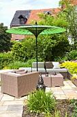 Korbmöbel auf Terrasse unter grünem Sonnenschirm