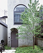 A tree and an entrance area in front of The Tower House, Tokyo, Japan