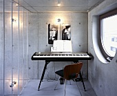 A music room with a keyboard and a chair against an exposed concrete wall