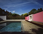 Modern architecture - a pink wall with a wooden bench in front of a pool