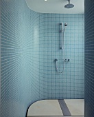 A shower cubicle with a curved wall and turquoise mosaic tiles