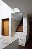 A modern, newly built house with a flight of marble and wood stairs