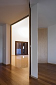 A modern anteroom with parquet flooring and an open doorway with a view into an empty room