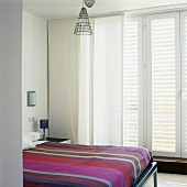 A modern bedroom with striped bedclothes on a double bed with curtains at the window