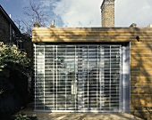 A modern, newly built house with wood panelling and a closed blinds at the windows