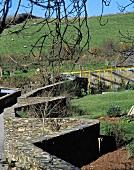 Moderne Gartengestaltung mit rustikaler Natursteinmauer