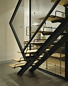 An open staircase with metal stairs and a banister with chicken wire