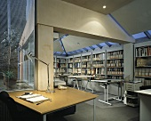 An architects office with an illuminated desk and a drawing table in front of a built in shelf