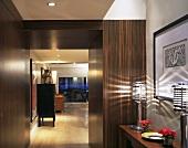 Flur mit Einbauten aus tropischem Holz und Blick durch offenen Durchgang in Wohnraum