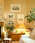 Schwarzweiss-Fotografien über Holztruhe mit brennender Lampe in modernem Wohnzimmer in Naturfarben