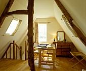Schreibtischplatte mit Regiestühlen vor antiker Kommode in ausgebautem Spitzboden mit Dachflächenfenstern