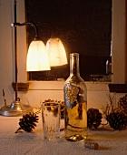 Brennende, antike Metalllampe, Weinflasche und Tannenzapfen vor blindem Spiegel