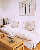 Naturfarben in moderner Sitzecke mit abstrakter Malerei über Polstersofa und Lampe mit Baumstamm-Fuss