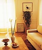 Zimmerpflanze auf Podest und holzgerahmte Bilder auf Fischgrätparkett in modernem Wohnzimmer in Naturfarben