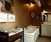 Wohnliches Badezimmer mit antiker Kommode und Spiegel neben weisser Wanne mit Kassettenverkleidung vor nougatfarbener Wand