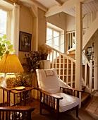 Edwardian Sessel mit weissen Polstern und gelber Lampenschirm neben Treppenaufgang in französischem Landhaus