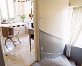 Blick auf Treppenabgang in Hellgrau neben offener Tür in lichtes Badezimmer mit Sessel in Scherenform