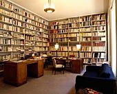 Grosse, alte Schreibtische und modernes, blaues Sofa in Bibliothek mit raumhohen, weissen Bücherregalen
