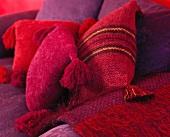 Veschiedene Chenille-Kissen in Rottönen auf lila Polstersofa