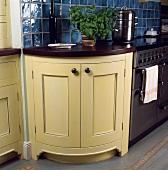 Viertelkreisförmig gebogener Küchenunterschrank im Shakerstil in moderner Küche mit Edelstahlherd und blauen Fliesen