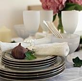 Frische Feige und bestickte Servietten mit silbernem Efeublatt auf Tellerstapel