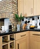 Moderne Küche aus hellem Holz und Granit-Arbeitsfläche mit Sekt in Würfelregal und Kaffeebereiter vor Kaminwand aus Backstein