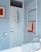 Grosser, gebogener Handtuchheizkörper neben weisser Kassettentür in modernem, pastellblauem Bad