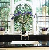 Blaue Iris vor vergittertem Rundbogenfenster über altmodischem Wasserhahn in schwarzer Küchenarbeitsfläche