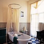 Freistehende Badewanne mit Vorhang an kreisrunder Stange als Duschkabine in Landhaus-Badezimmer