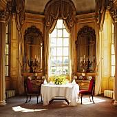 Mit bodenlanger, weisser Tischdecke festlich gedeckt in georgianischem Esszimmer-Erker mit Kerzenleuchtern vor antiken Spiegeln zwischen hohen Fenster