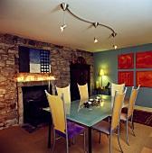 Esszimmer mit futuristischen, hochlehnigen Stühlen an Glastisch und Halogenspots im Kontrast mit Kamin in rustikaler Steinmauer