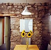 Modernes Esszimmer mit Edelstahlkühlschrank im Kontrast zu Natursteinmauer und Sonnenblumenstrauss auf Holztisch