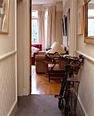 Altmodisches Fahrrad in kleinem Gang mit offener Tür zum traditionellen Wohnzimmer