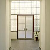 Eine Eingangshalle mit Glasbausteinen und Milchglastür