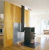 Schwarzer Eisenofen in einem offenen Wohnzimmer