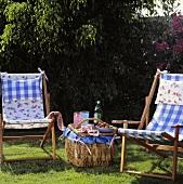 Korbtisch und Liegestühle auf dem Rasen im Garten