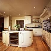 Kücheninsel mit integriertem Weinkühler in einer cremefarbenen Küche mit Holzboden