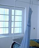 Blaues Kleid hängt auf dem weissen Metall-Bettgestell vor dem Fenster im Schlafzimmer