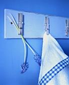 Handtuch und Blumen mit Wäscheklammern befestigt auf einem Brett auf blauer Wand