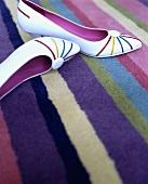 weiße Damenschuhe mit Streifen auf bunt gestreiftem Teppich