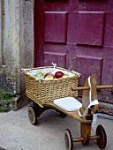 Ein Korb Äpfel auf einem Kinderdreirad aus Holz